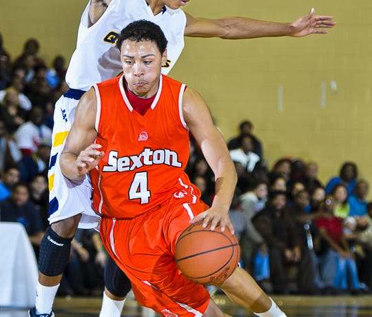 Bryn Forbes (4) of Sexton drives around Darryl Thompson of Eastern after faking him off his feet during their game Friday February 24, 2012 at Eastern High in Lansing.  KEVIN W. FOWLER PHOTO