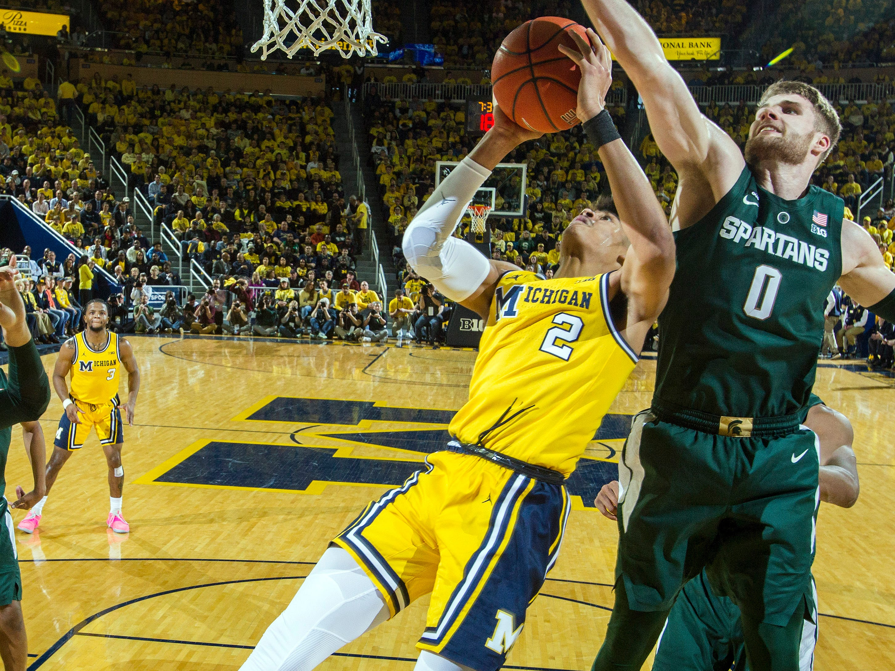 Michigan guard Jordan Poole (2) has his shot-attempt blocked by Michigan State guard Kyle Ahrens (0) in the first half of an NCAA college basketball game at Crisler Center in Ann Arbor, Mich., Sunday, Feb. 24, 2019.