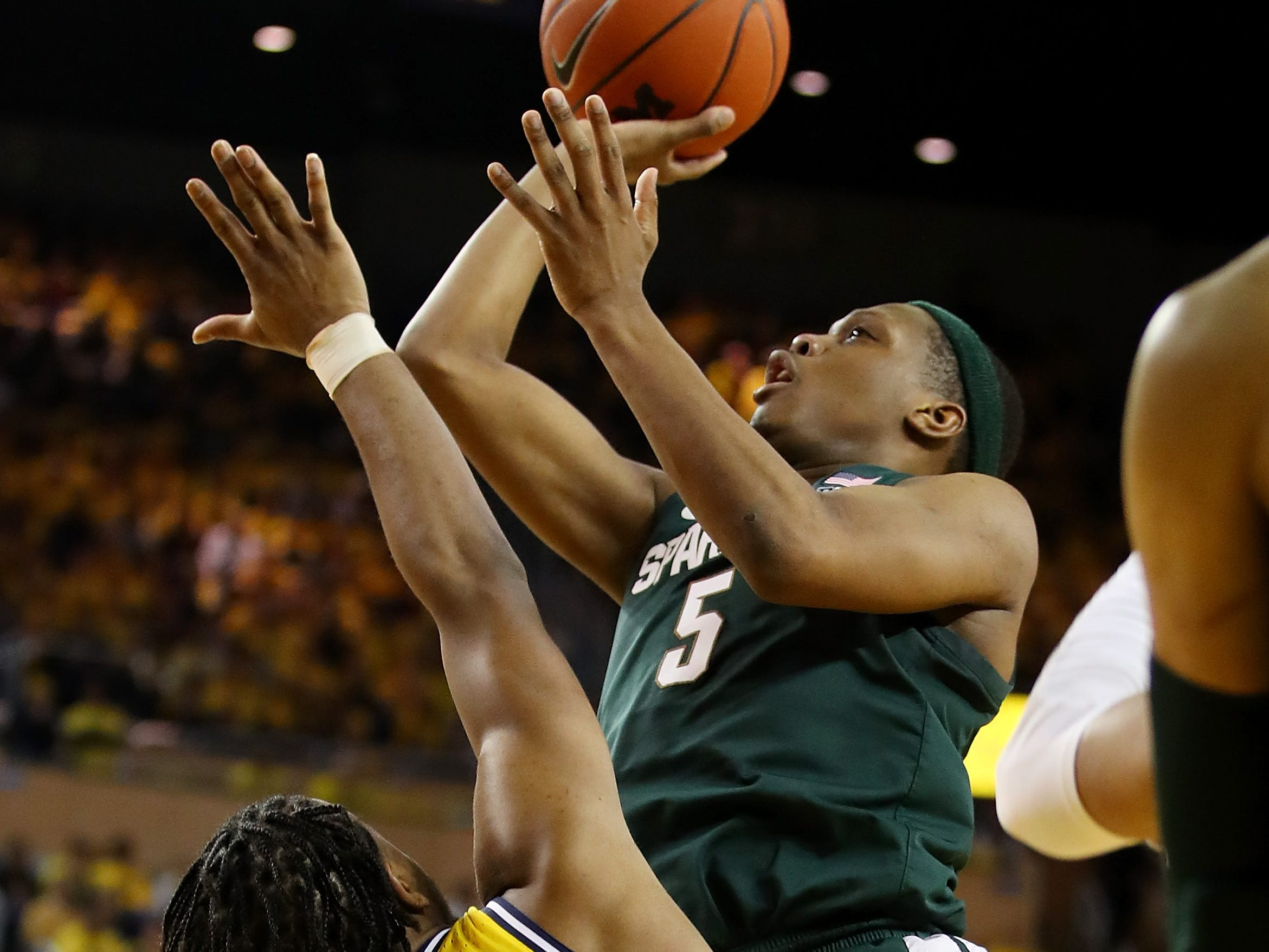 Cassius Winston #5 of the Michigan State Spartans takes a shot over Zavier Simpson #3 of the Michigan Wolverines during the second half at Crisler Arena on February 24, 2019 in Ann Arbor, Michigan. Michigan State won the game 77-70.
