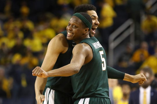 Cassius Winston #5 and Kenny Goins #25 of the Michigan State Spartans react after a 77-70 win over the Michigan Wolverines at Crisler Arena on February 24, 2019 in Ann Arbor, Michigan.