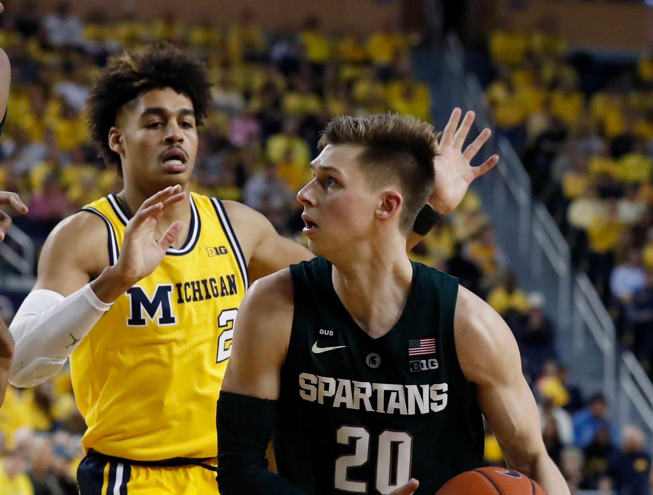 Michigan State guard Matt McQuaid (20) is defended by Michigan guard Jordan Poole (2) during the second half of an NCAA college basketball game, Sunday, Feb. 24, 2019, in Ann Arbor, Mich.