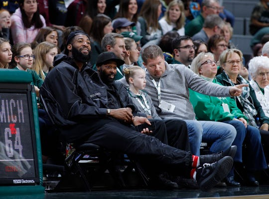 Detroit Pistons center Andre Drummond, left, watches from courtside during an NCAA college basketball game between Michigan and Michigan State, Sunday, Feb. 24, 2019, in East Lansing, Mich. Michigan State won 74-64. (AP Photo/Al Goldis)