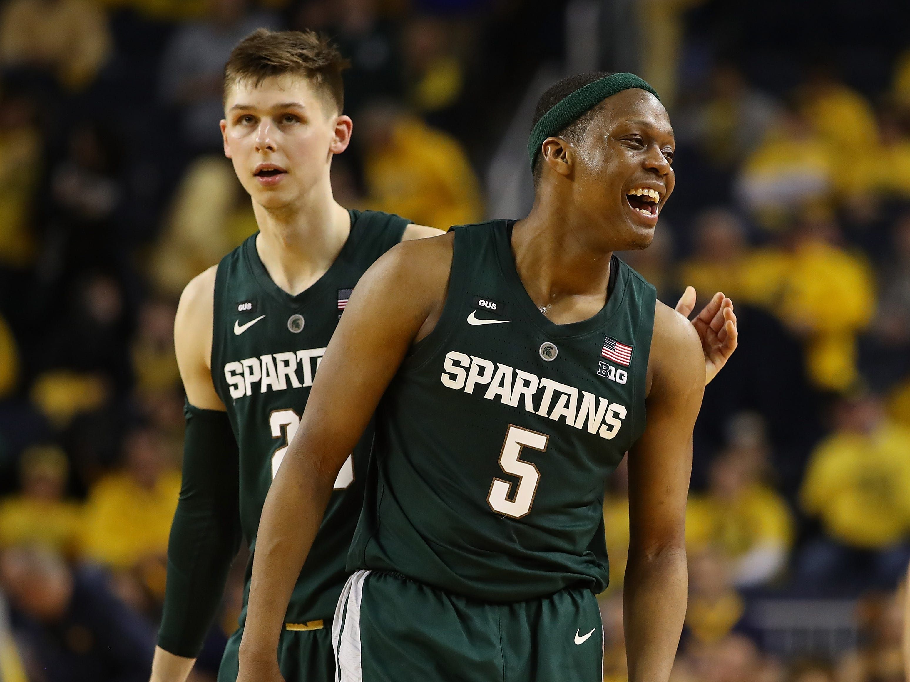 Cassius Winston (5) and Matt McQuaid celebrate a basket late in Michigan State's win over Michigan on Feb. 24, 2019 in Ann Arbor.
