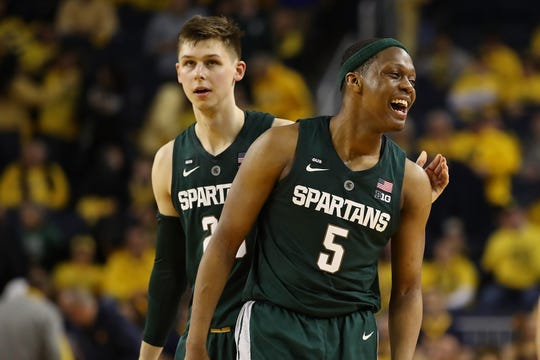 Cassius Winston (5) and Matt McQuaid celebrate a basket late in Michigan State's win over Michigan on Feb. 24, 2019 in Ann Arbor.