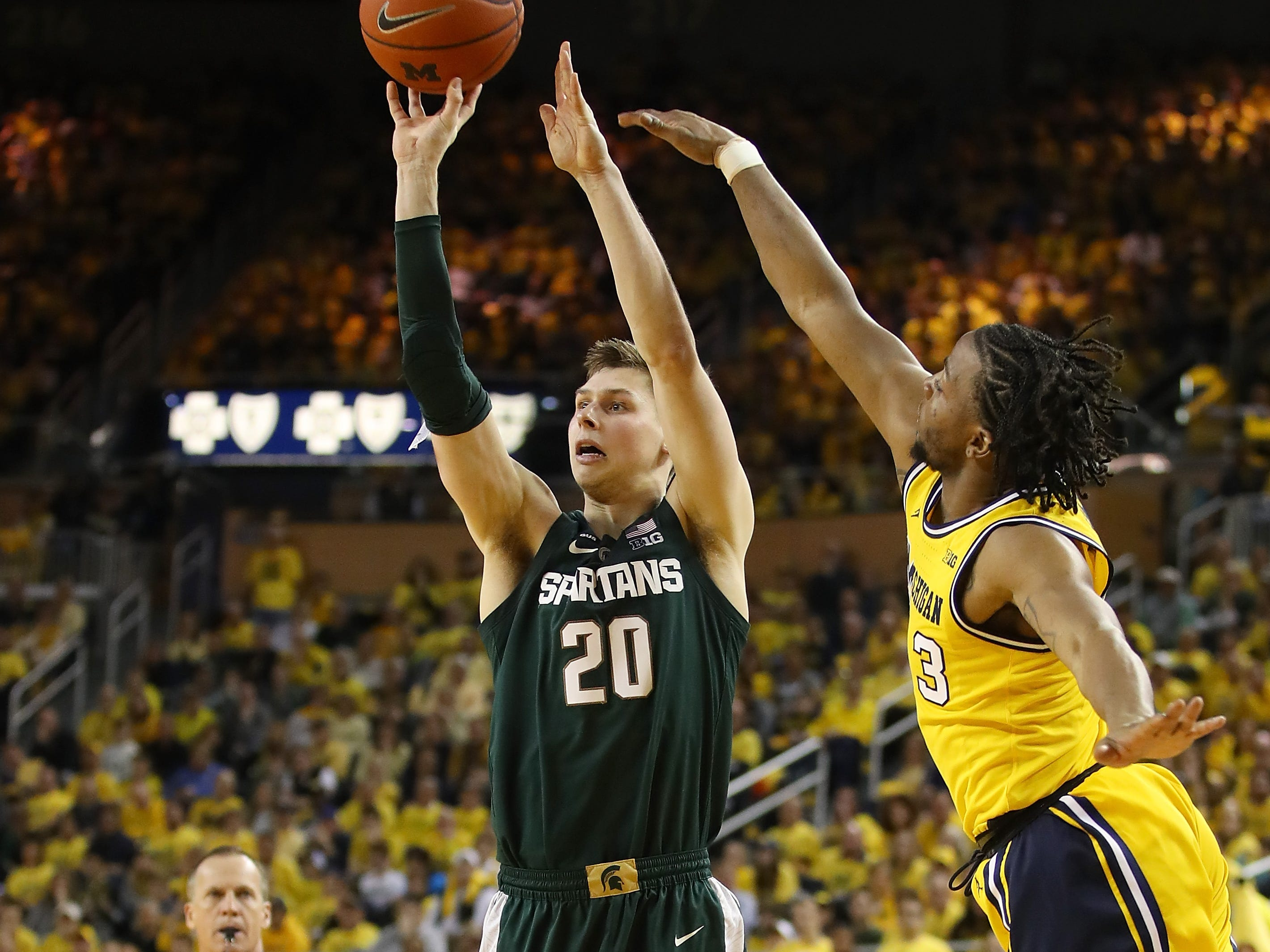 Matt McQuaid #20 of the Michigan State Spartans takes a shot next to Zavier Simpson #3 of the Michigan Wolverines during the second half at Crisler Arena on February 24, 2019 in Ann Arbor, Michigan. Michigan State won the game 77-70.