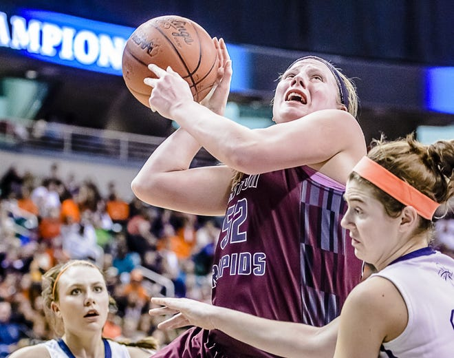 Allie Dittmer (center) of Eaton Rapids takes the ball to the basket in the state semifinal against Flint Powers Catholic.