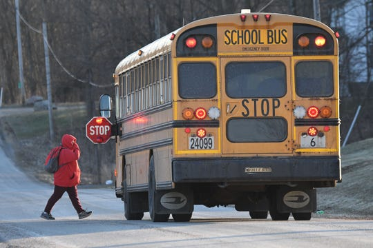 A student crosses the street before boarding an Ontario Schools bus on a chilly Monday morning.