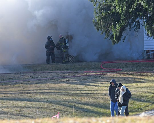 Residents of 182 Timmerman Road leave their home as it burns Monday morning.