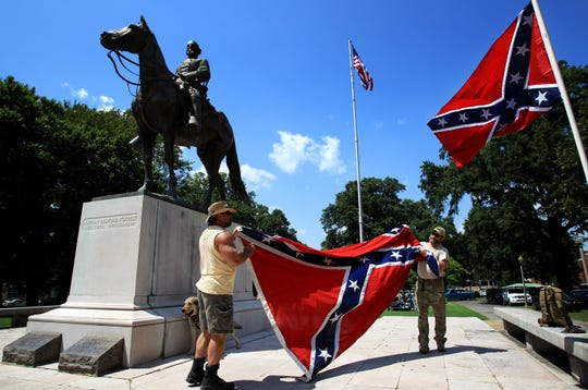 July 12, 2015 - Mike Goza (left) helps Mike Junor fold a confederate flag after they were asked to remove it from the base of the statue and grave of civil war general Nathan Bedford Forrest during a celebration of the civil war general's 194th birthday. (Mike Brown/The Commercial Appeal)
