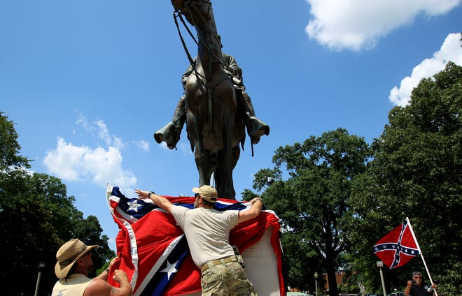 Mike Goza, left, helps Mike Junor drape a Confederate flag over the base of the statue and grave of Civil War general Nathan Bedford Forrest on July 12, 2015. They removed the flag at the request of organizers during an event that was as much a rally in support of the Confederate flag as it was to celebrate Forrest's birthday.