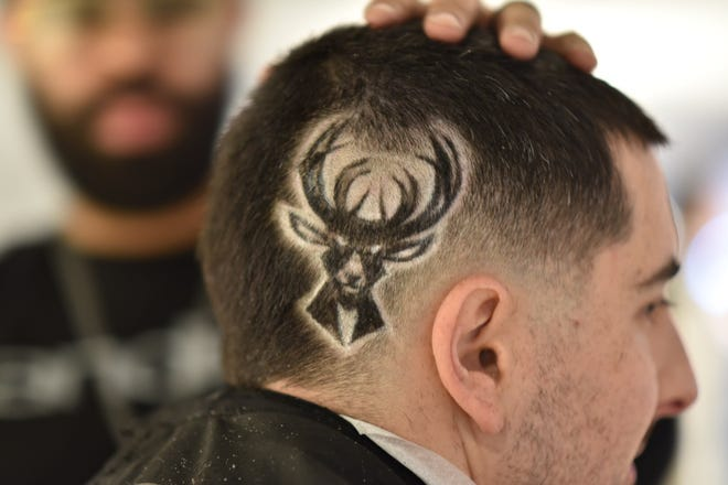 David Farby shows off the Bucks logo in his head, trimmed into place by NBA barber Kenny Duncan.