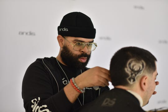 NBA barber Kenny Duncan designs a Bucks logo into the side of David Farby's head.