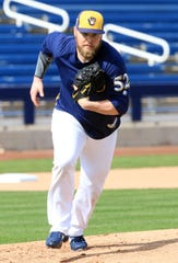 Milwaukee Brewers pitcher Jimmy Nelson heads to cover first base during spring training drills.