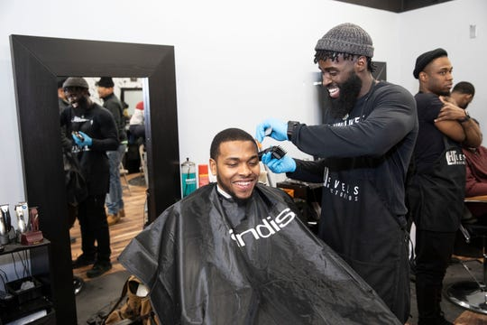 """Sterling Brown sits in the chair for a haircut Feb. 18 during a Bucks-sponsored """"Barbershop Monday"""" event. Milwaukee-based barbers give between 20 and 30 free haircuts at each session."""