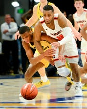 Marquette forward Jamal Cain (left) and Carroll guard Ray Pierce chase down a loose ball in the first half of an exhibition game at Fiserv Forum.