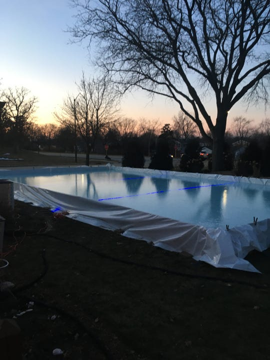 Matt Medvecz's backyard ice rink in Greendale measures about 40 feet by 80 feet. He installed blue lights in the ice to mark the rink off in thirds.
