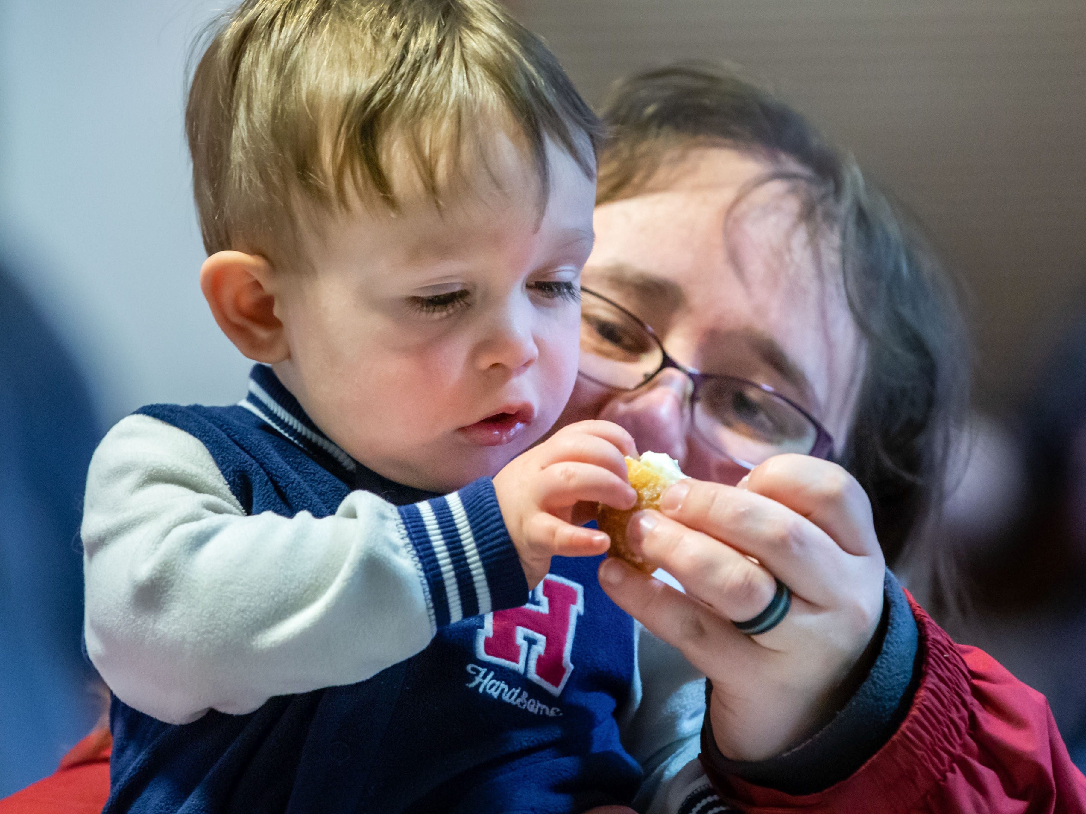Sixteen-month-old SJ Laturi of Milwaukee samples a paczek with a little assistance from his mom Jamie during the Wisconsin Bakers Association's Paczki Preview Party at the Polish Center of Wisconsin in Franklin on Sunday, Feb. 24, 2019. The event, which showcases some of the best paczki from the area, also features live music, a special guest appearance by Little Miss Polish Fest and more.