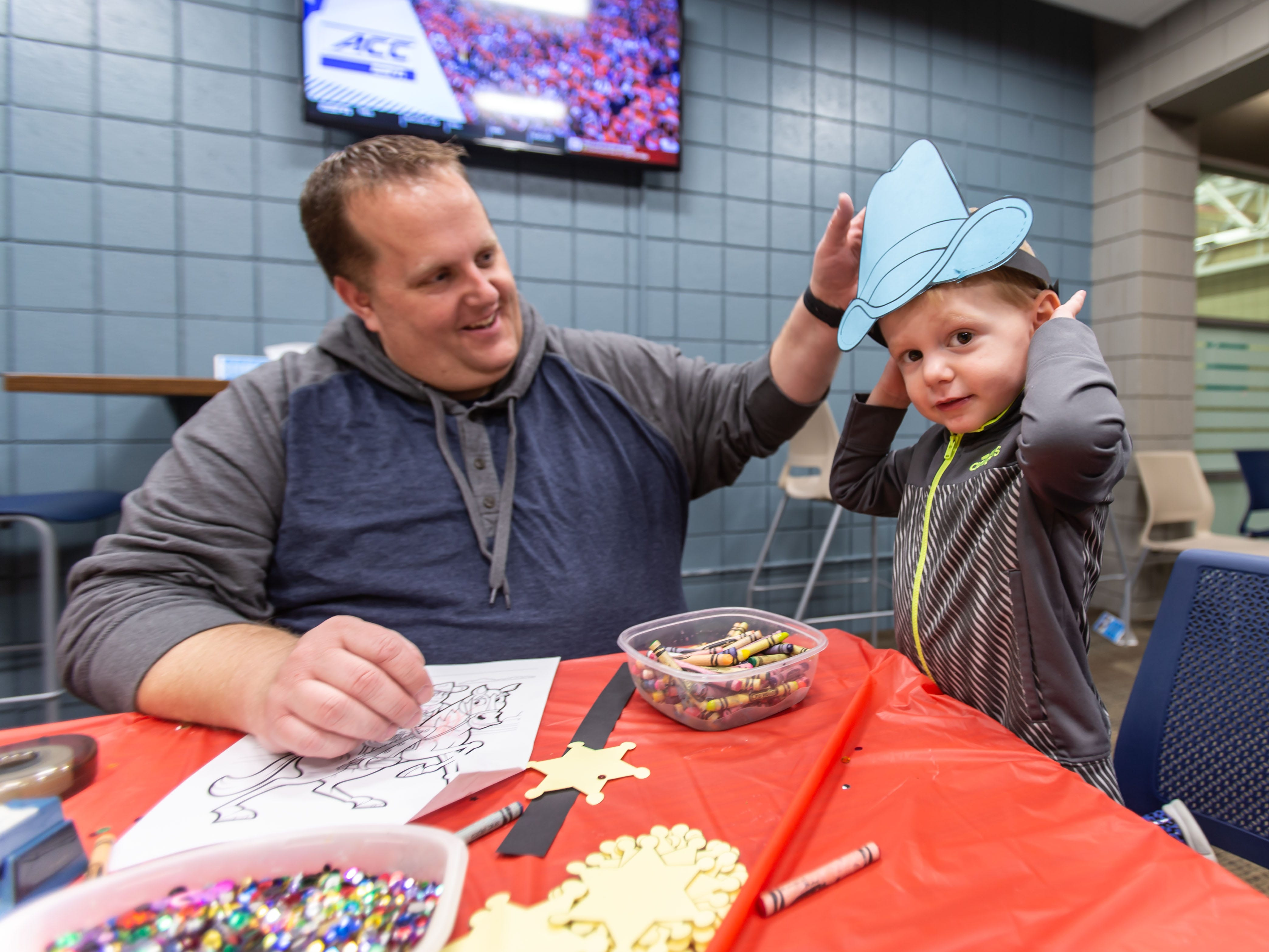 Three-year-old Logan Husslein of Germantown tries on a cowboy hat he made with his dad Jason during the Hometown Hoedown NEA Big-Read Kickoff Event at the Tri County YMCA in Menomonee Falls on Saturday, Feb. 23, 2019. The event featured live music, food, games, and western themed activities for the whole family.