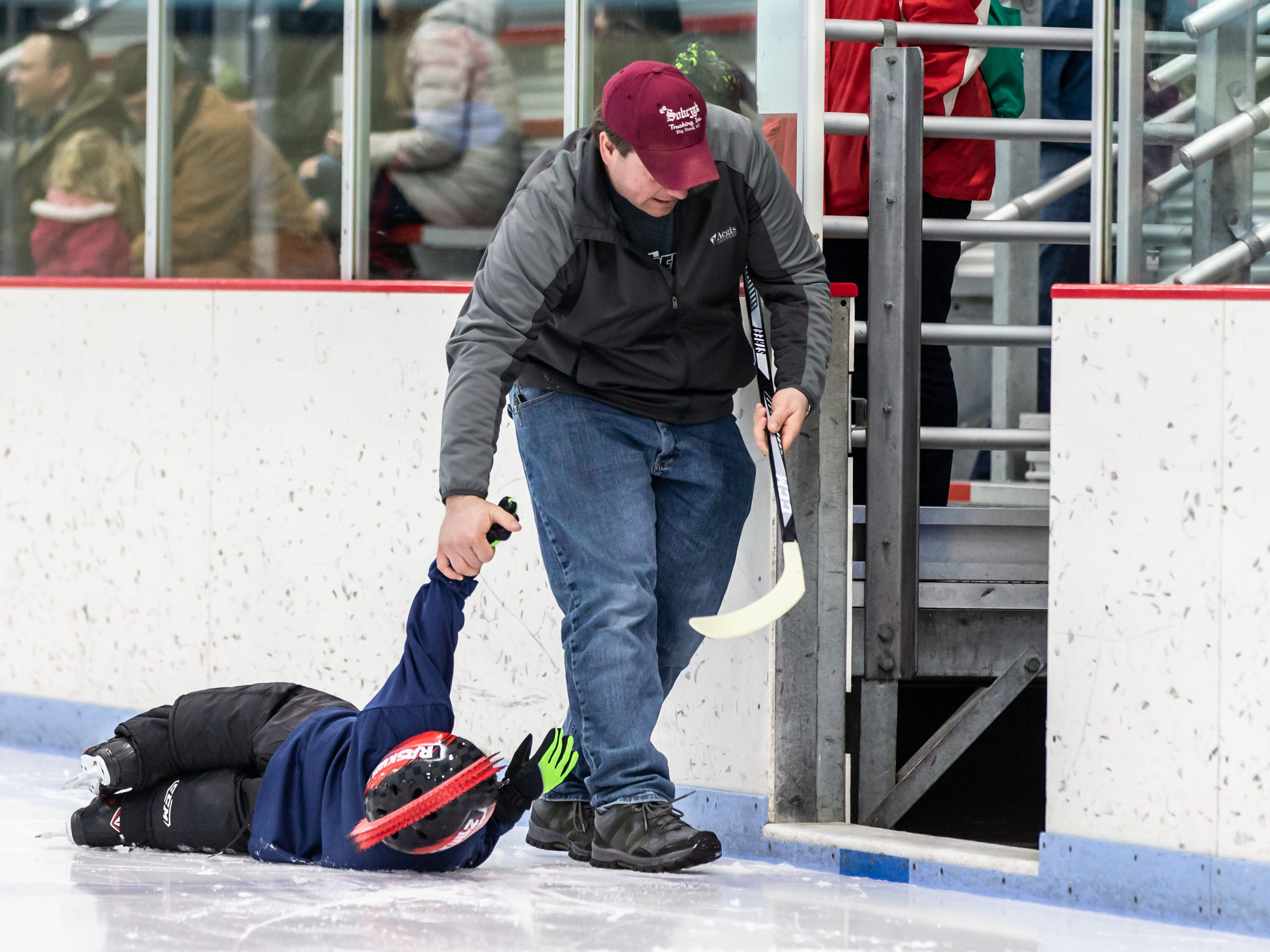 Five-year-old Luke Maduscha of Ixonia runs out of energy and gets a tow by his dad Andy during the Try Hockey For Free Day at the Howard G. Mullett Ice Center in Hartland on Saturday, Feb. 23, 2019.