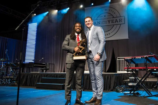 D'Cota Dixon (left) accepts Collegiate Man of the Year award from Jason Witten