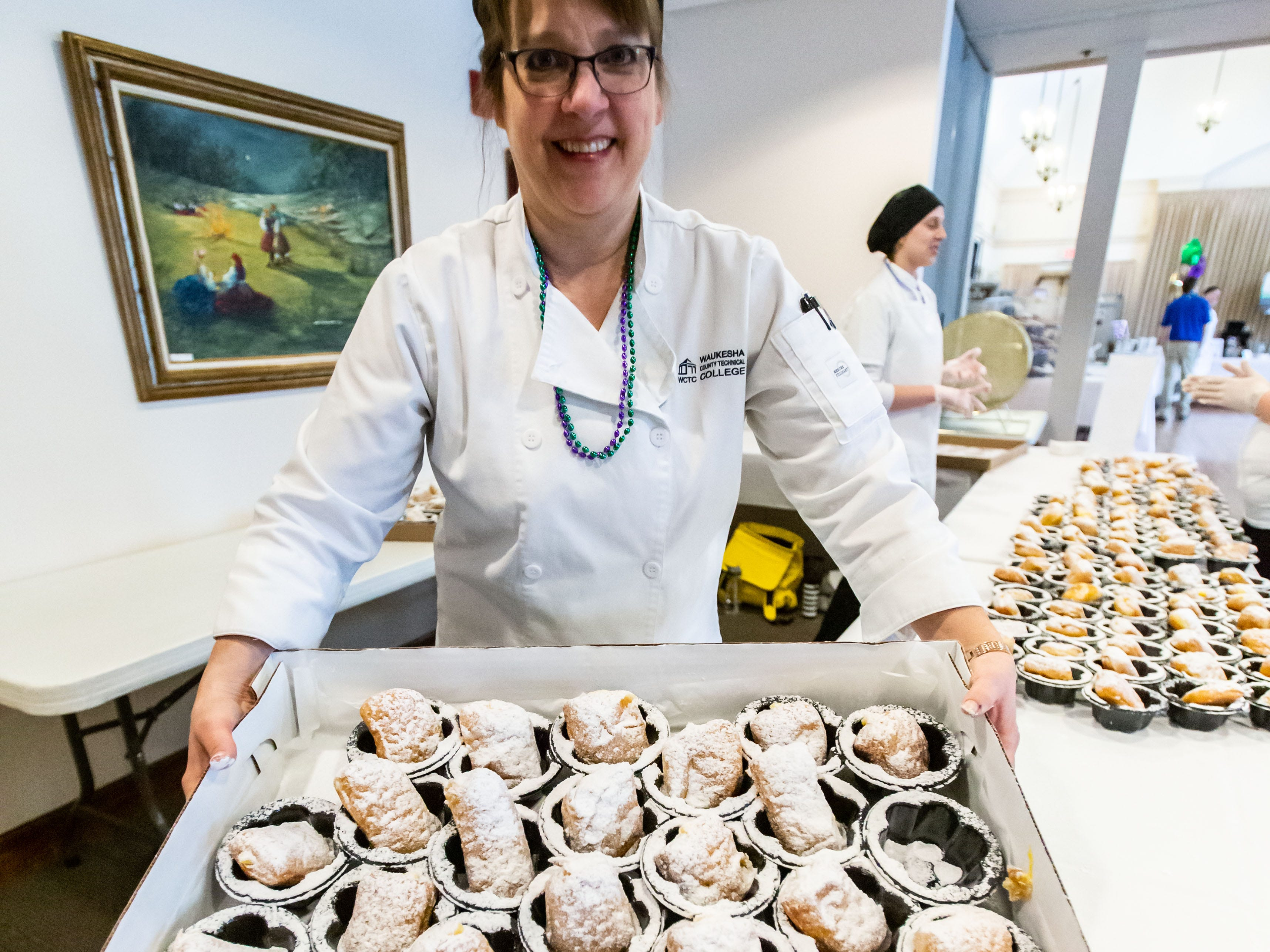 Mona Gramberg of Neat-O's Bake Shoppe unloads a fresh tray of paczki during the Wisconsin Bakers Association's Paczki Preview Party at the Polish Center of Wisconsin in Franklin on Sunday, Feb. 24, 2019. The event, which showcases some of the best paczki from the area, also features live music, a special guest appearance by Little Miss Polish Fest and more.