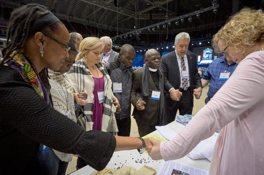 Delegates pray together during the February 23, 2019, opening session of the Special Session of the General Conference of The United Methodist Church.