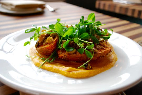 Spiced sweet potato rounds on tahini-laced sweet potato puree, topped with golden raisins, pistachios, preserved lemon and pea shoots from Bells Bend Farms.