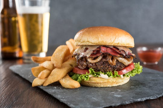The Pastrami Burger at TooJay's Deli features juicy sirloin rolled in a pastrami rub and topped with pastrami, caramelized onions, Swiss cheese and chipotle mayonnaise.