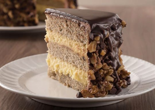 Banana Dream Cake at TooJay's Deli features rich banana cream, chocolate chips, walnuts and milk chocolate ganache.
