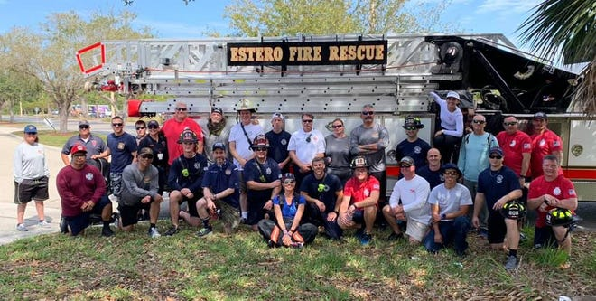 People gather for a photo in front of an Estero Fire Rescue truck on the second day of the My Brothers' Burden walk on Monday, Feb. 25, 2019.