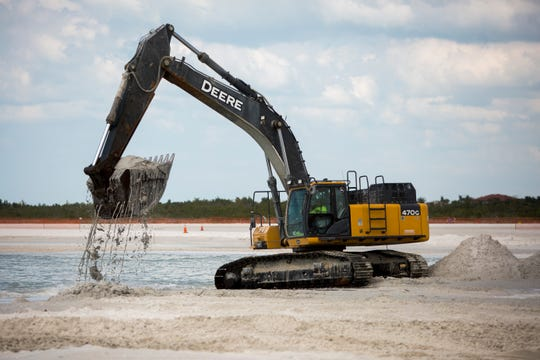 A backhoe pulls sand from the shoreline Tuesday, Feb. 19, 2019. The heavy equipment is operated by Earth Tech Enterprises as part of a $1.1 million beach regrading project in Marco Island.