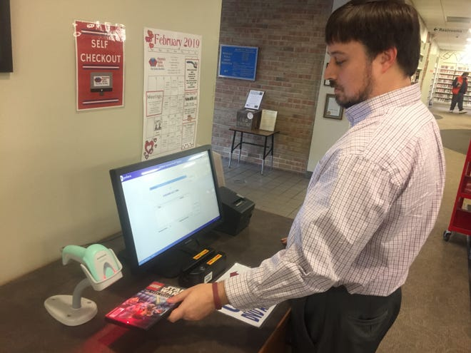 Pataskala Public Library Director Jeff Rothweiler demonstrates the new self-checkout station.