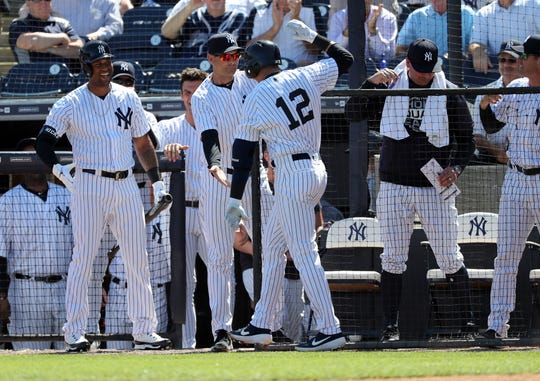 New York Yankees shortstop Troy Tulowitzki (12) is congratulated by manager Aaron Boone (17) and center fielder Aaron Hicks (31) after hitting a home run during the first inning against the Toronto Blue Jays  at George M. Steinbrenner Field.