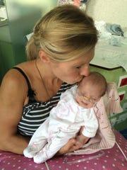 Kim Kurzow Spratt kisses her daughter, Hayden Grace, at a hospital in Portugal.