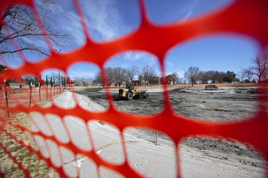 Orange fencing forms a barrier around the drained Young Park pond on Monday, Feb. 25, 2019. The pond area is closed off, as the city undertakes a restoration project. However, the broader park is still open to visit.