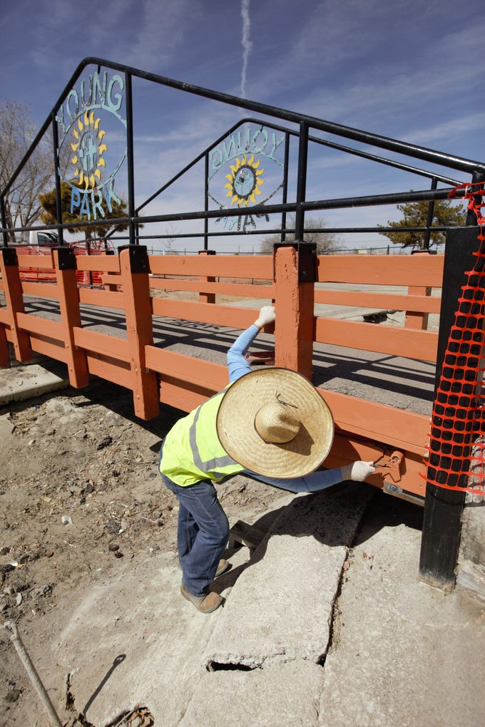 Joe Maez with the city of Las Cruces parks maintenance and construction division paints a portion of a newly repaired bridge at Young Park in Las Cruces on Monday, Feb. 25, 2019.