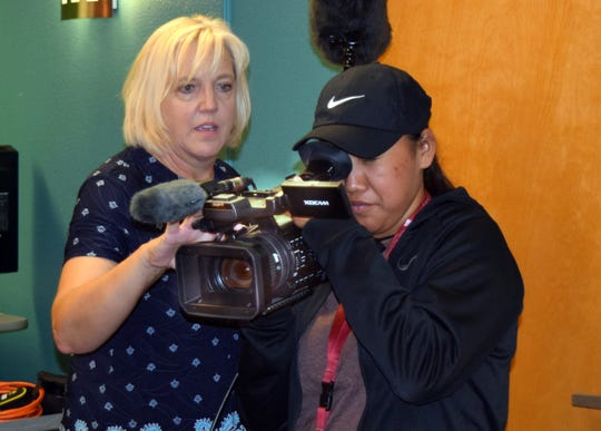 Tomilee Turner, left, associate director of Innovative Media Research and Extension, video production department, of New Mexico State University's College of Agricultural, Consumer and Environmental Sciences, shows DreamKeepers participant Valissidy Sam how to use a video camera.