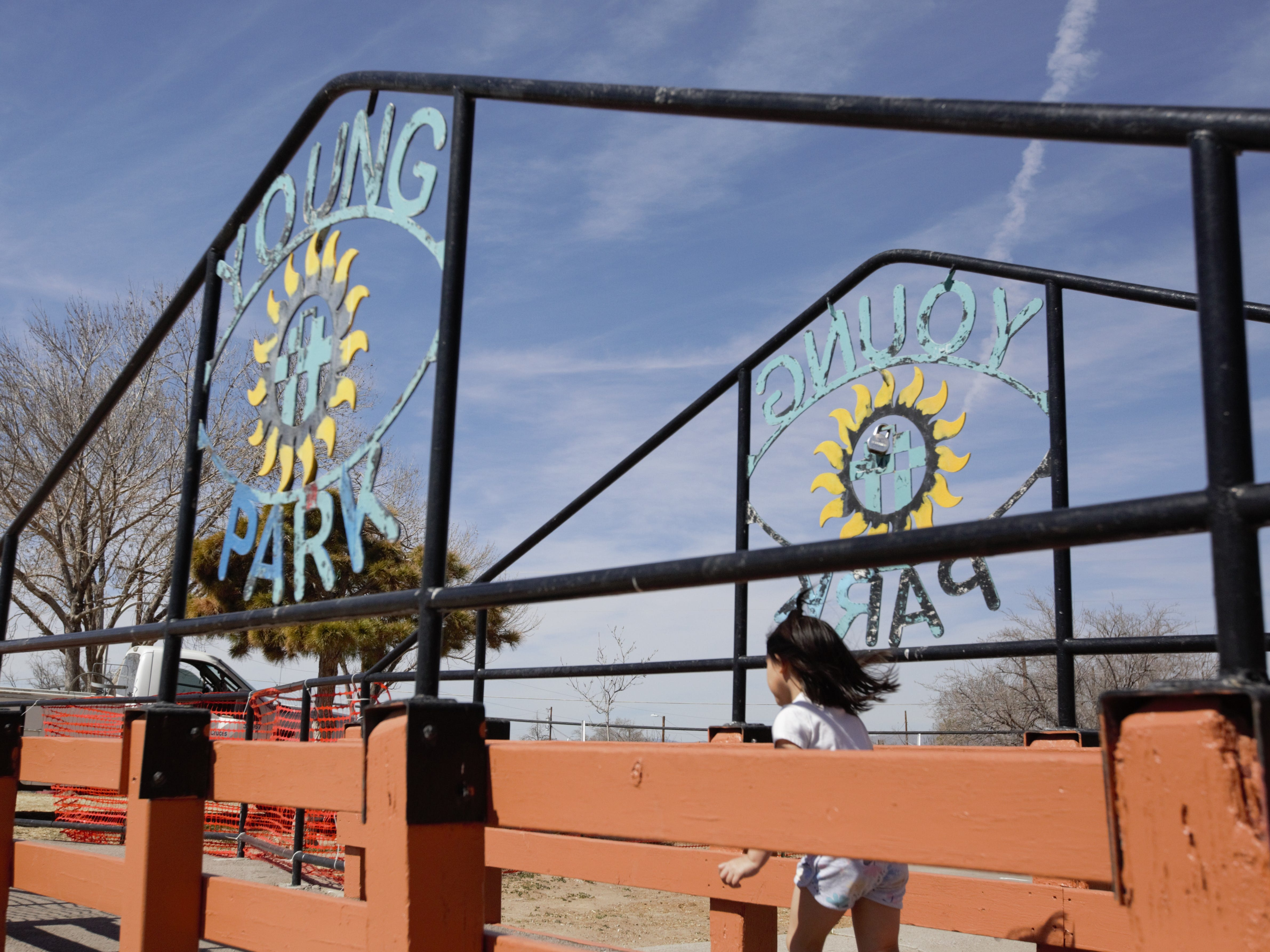 Katelyn Guzman, 4, dashes past iconic signs at Young Park on Monday, Feb. 25, 2019. The metal signs will be repainted in coming days as part of an ongoing pond refurbishment project.