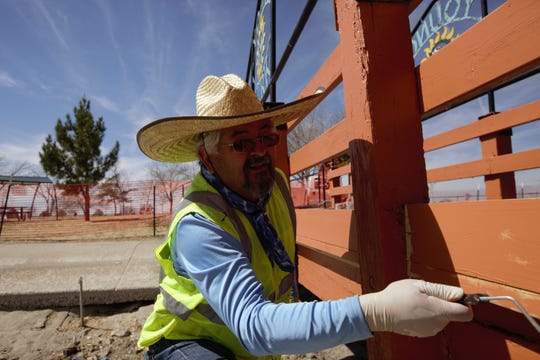 Las Cruces parks employee Joe Maez paints newly installed wood on a bridge at the Young Park Pond on Monday, Feb. 25, 2019.