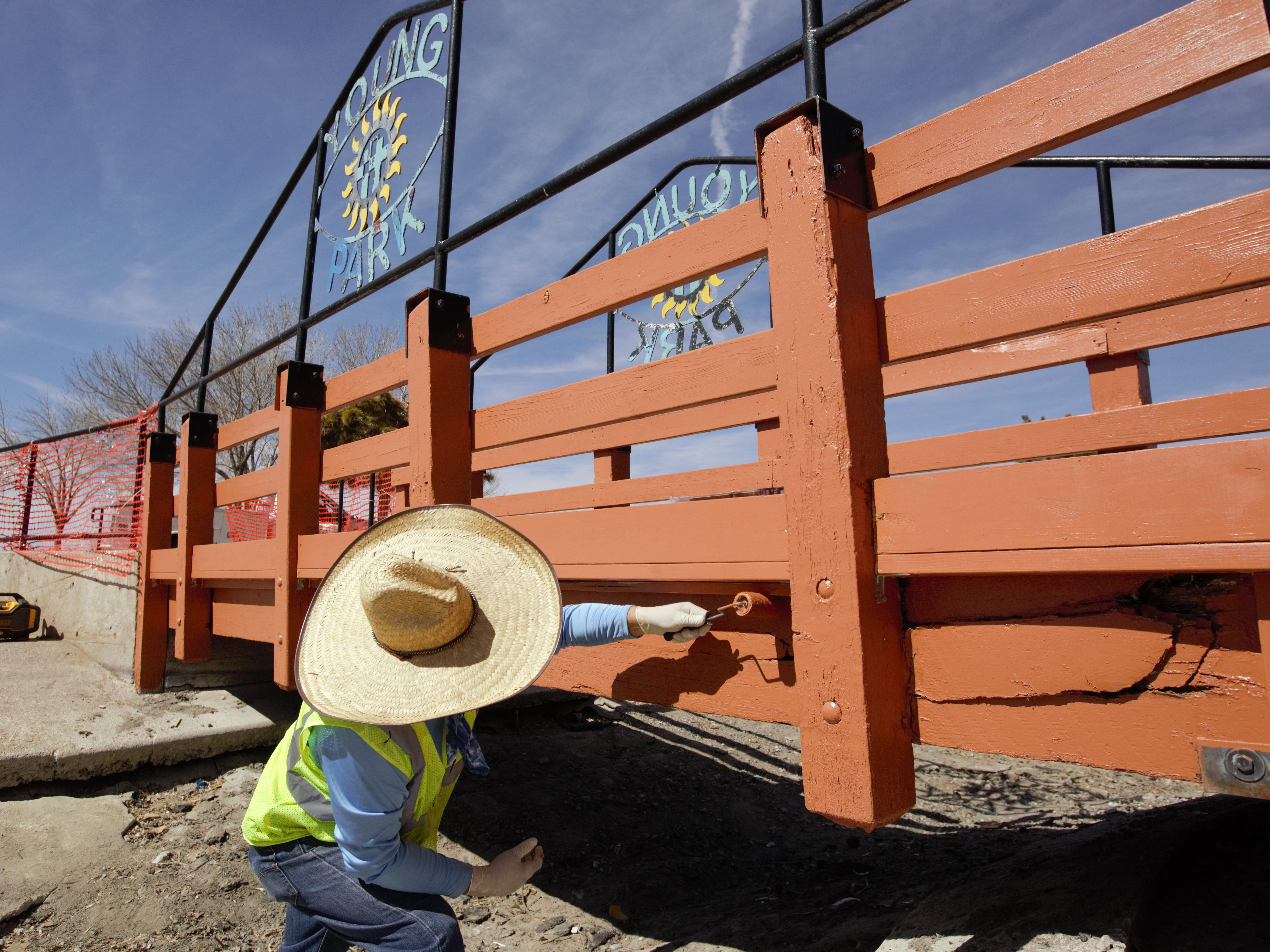 City parks employee Joe Maez paints a portion of a bridge at Young Park on Monday, Feb. 25, 2019, as part of an ongoing park and pond refurbishment.