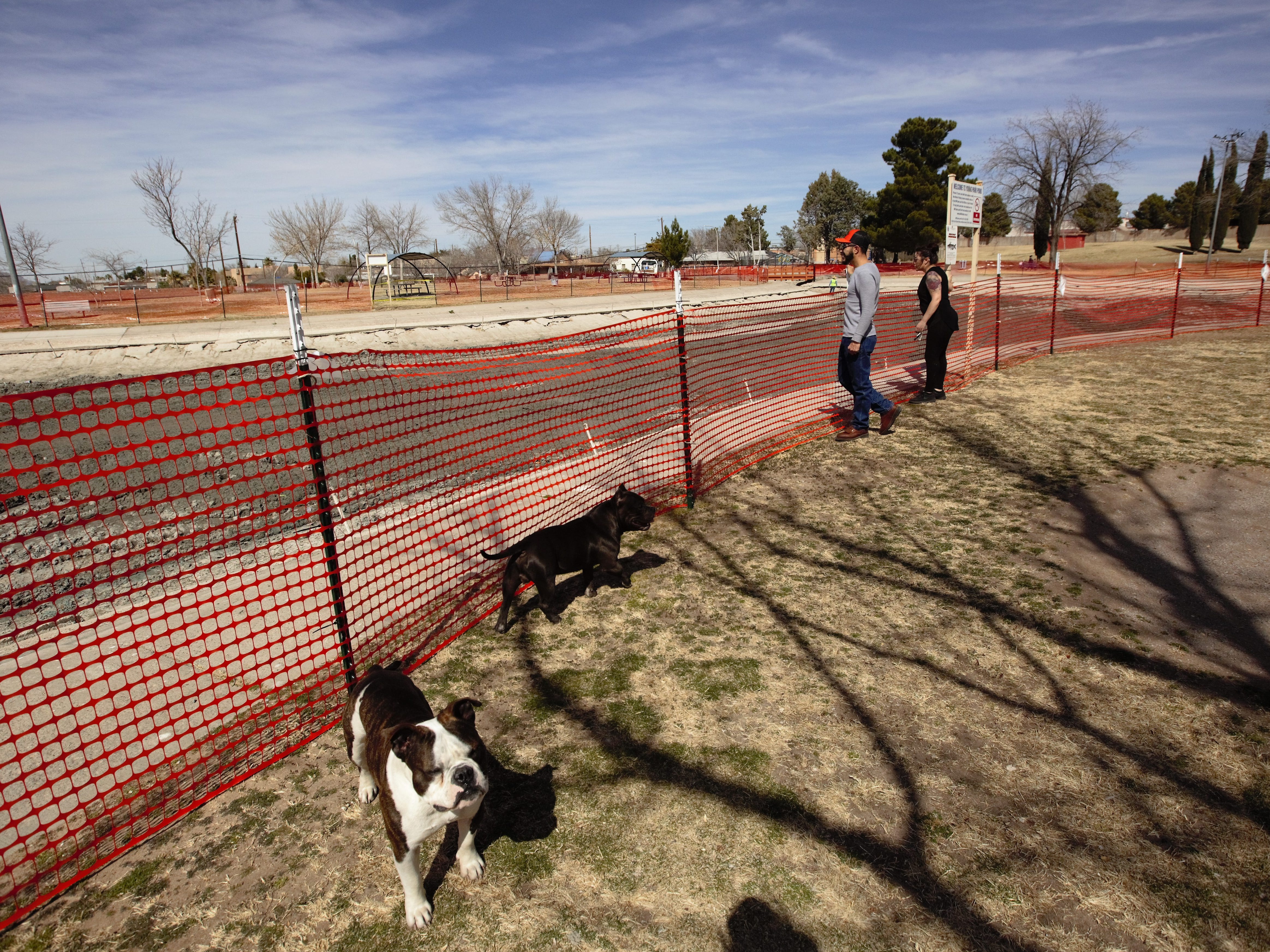 Cindy Flores, right, and Raymond Baca, both of Las Cruces, survey an ongoing Young Park Pond restoration on Monday, Feb. 25, 2019, as their dogs, Chopper and Kodak, walk nearby.