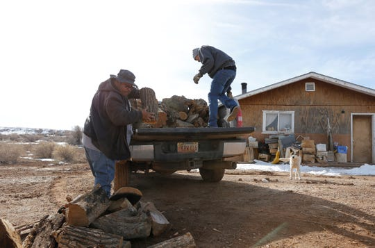 Alvin Gould, left, and Demetrius Begaye unload firewood at a residence in Newcomb on Monday.