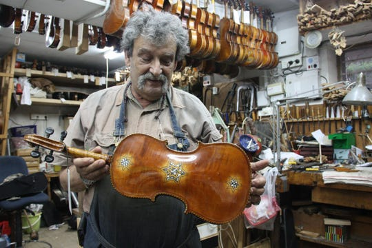 Israeli violinmaker Amnon Weinstein working on a violin in his workshop.
