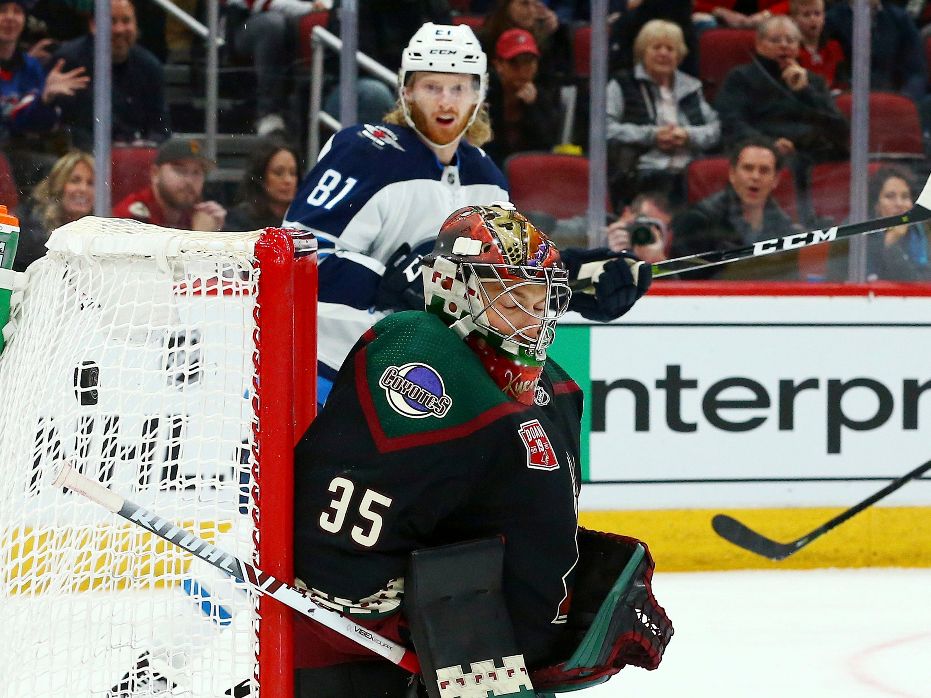 Arizona Coyotes goaltender Darcy Kuemper (35) gives up a goal to Winnipeg Jets' Patrik Laine as Jets left wing Kyle Connor (81) looks on during the first period of an NHL hockey game Sunday, Feb. 24, 2019, in Glendale, Ariz.