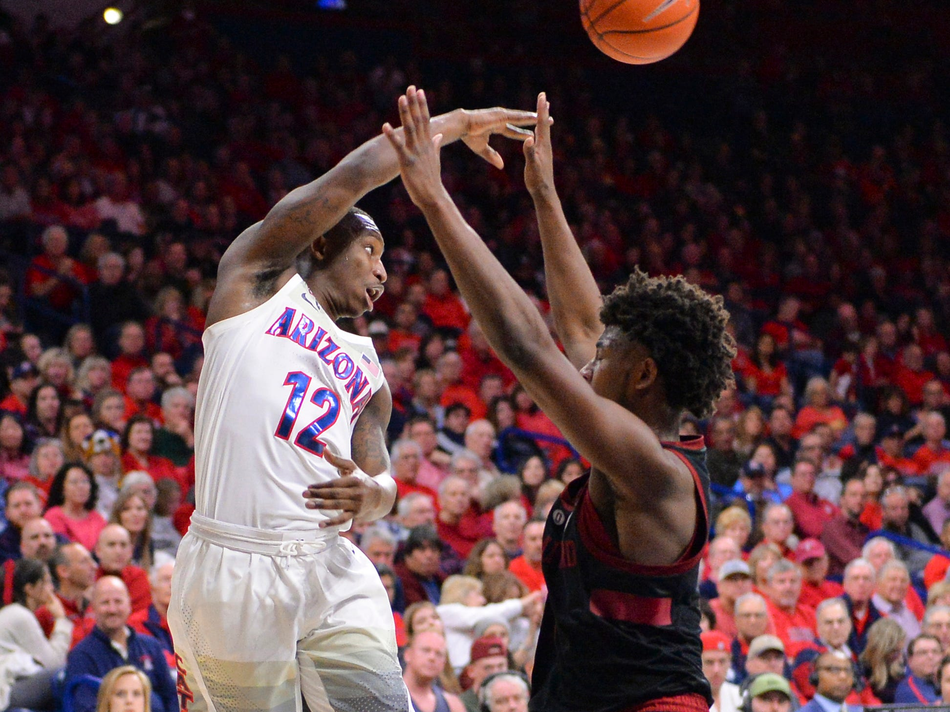 Feb 24, 2019: Arizona Wildcats guard Justin Coleman (12) passes the ball over Stanford Cardinal guard Daejon Davis (1) during the second half at McKale Center.