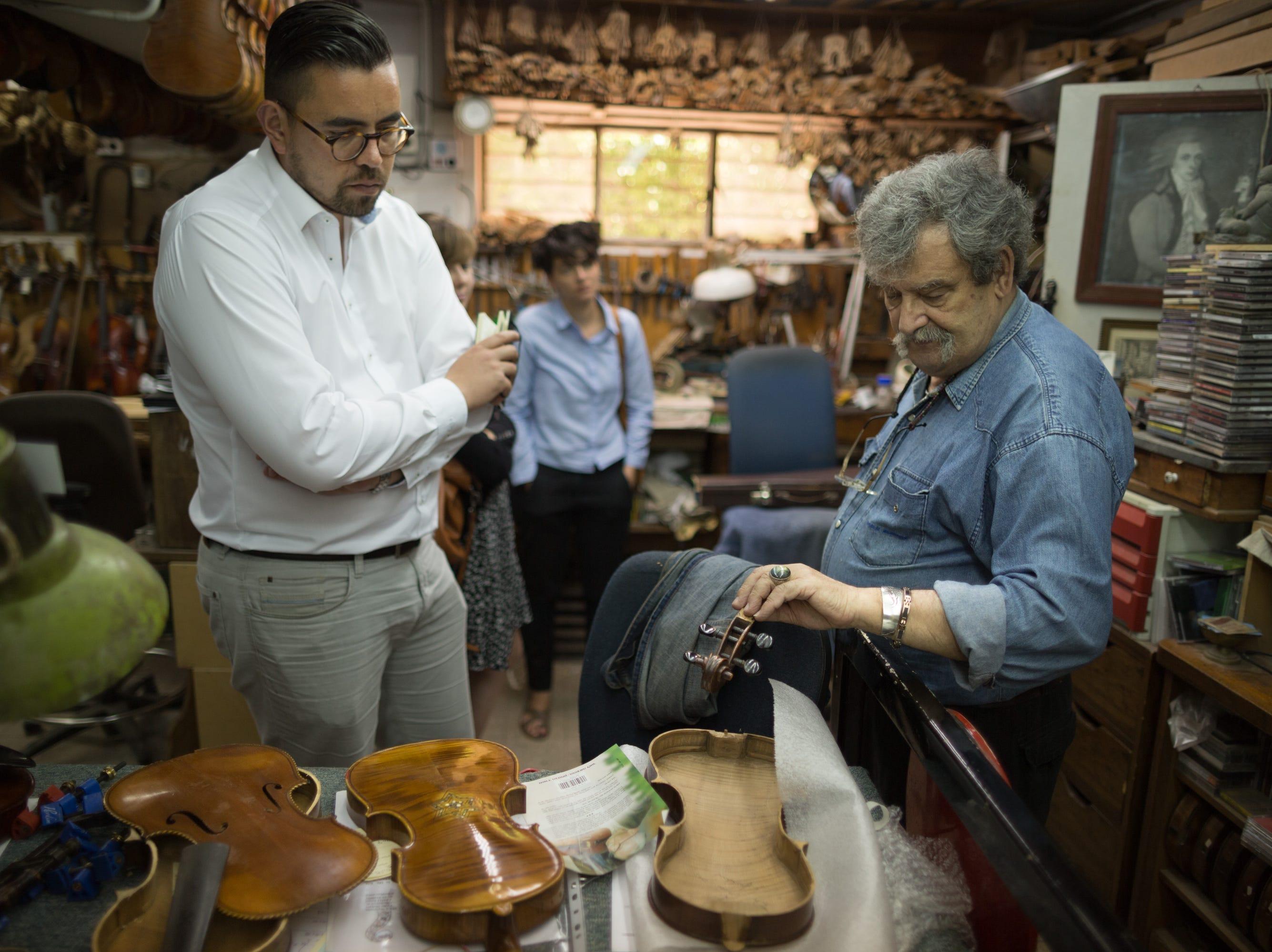 Israeli violinmaker Amnon Weinstein examining violins in his workshop.