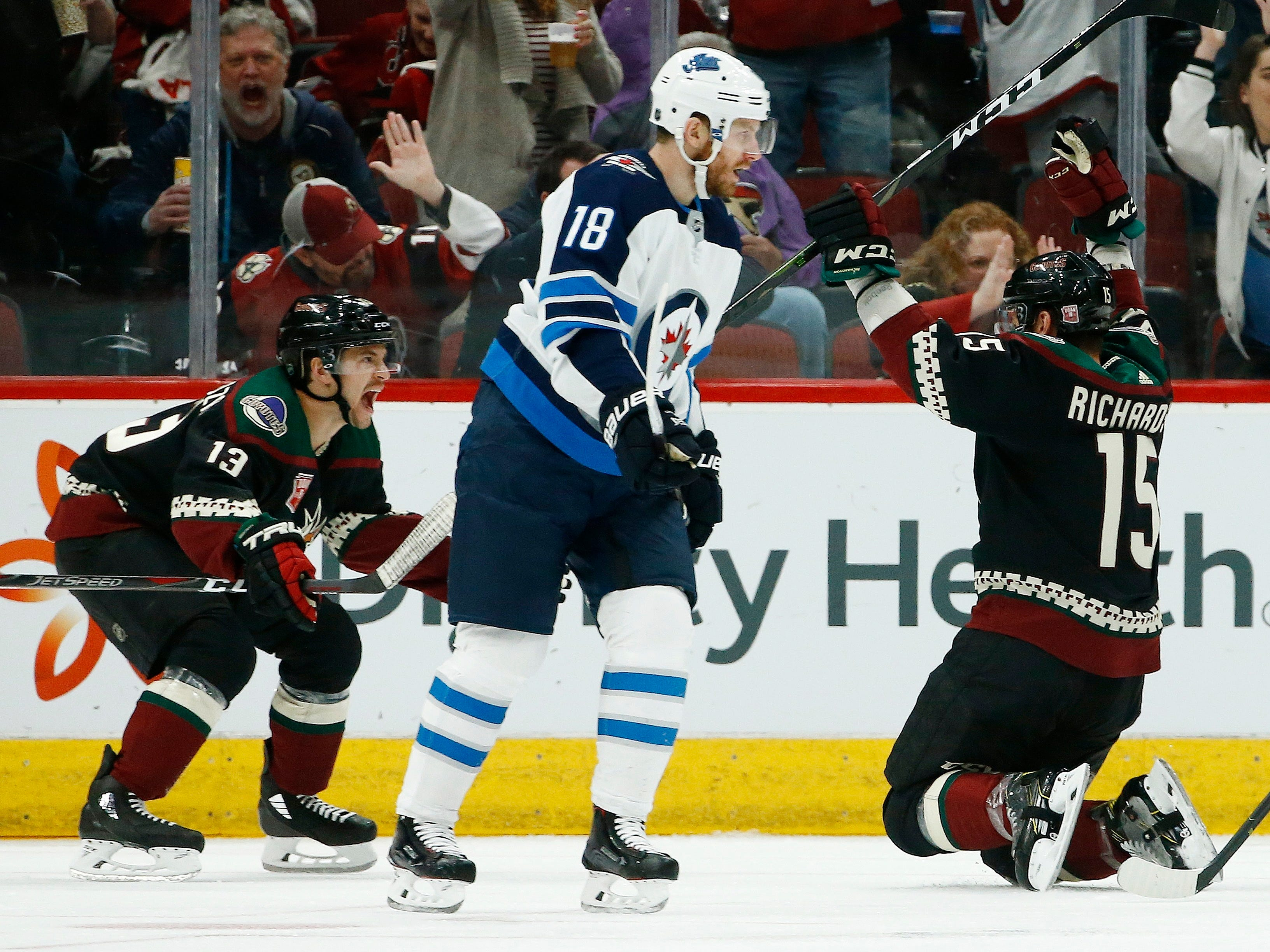 Arizona Coyotes center Brad Richardson (15) celebrates his goal against the Winnipeg Jets with Coyotes' Vinnie Hinostroza (13) as Jets center Bryan Little (18) skates past during the first period of an NHL hockey game Sunday, Feb. 24, 2019, in Glendale, Ariz.