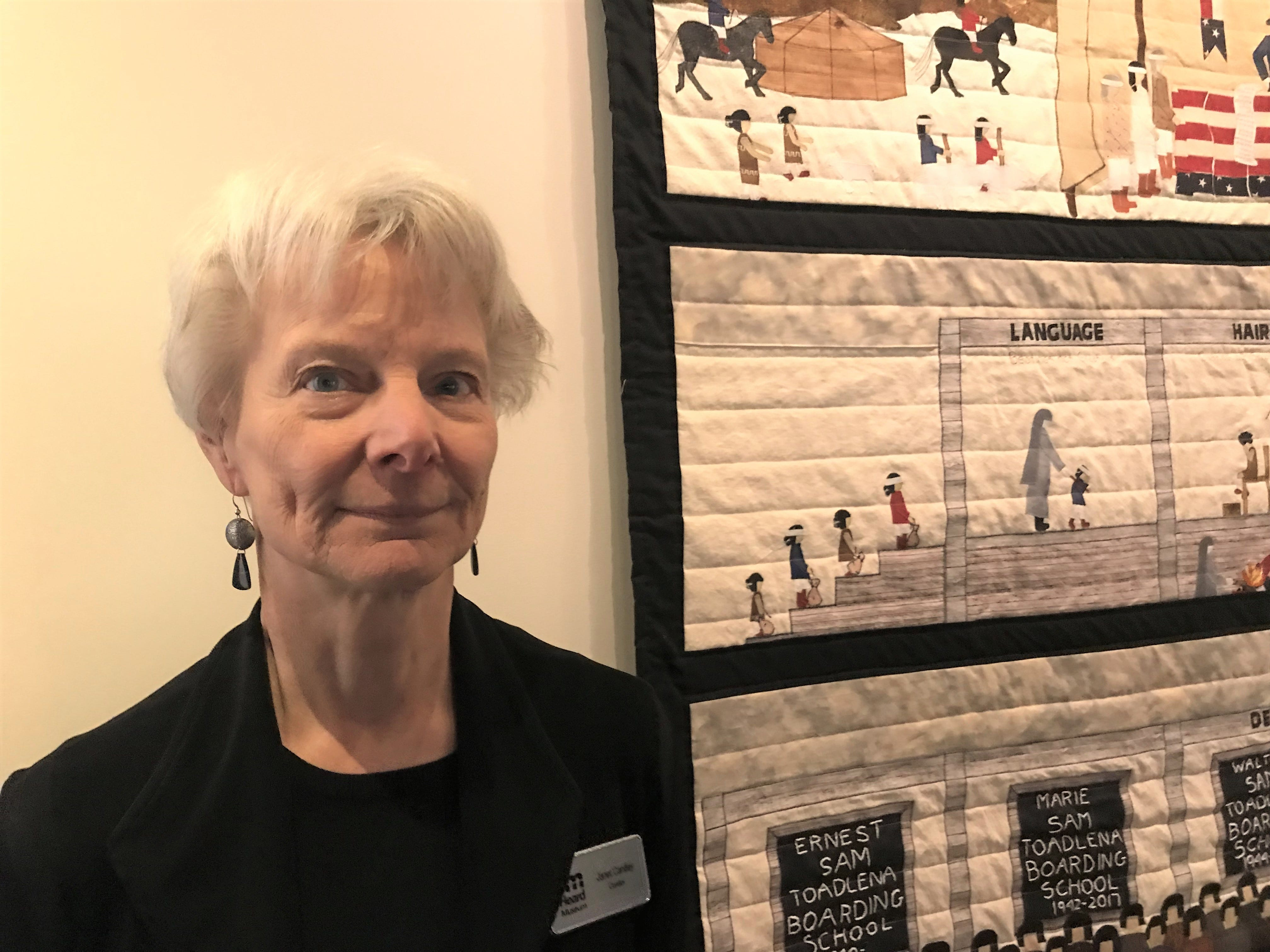 """Heard Museum Curator Janet Cantley stands by the quilt made by Navajo weaver Susan Hudsan in honor of her family who went to boarding schools. The quilt is part of the Heard Museum's """"Away From Home: American Indian Boarding School Stories"""" exhibit."""