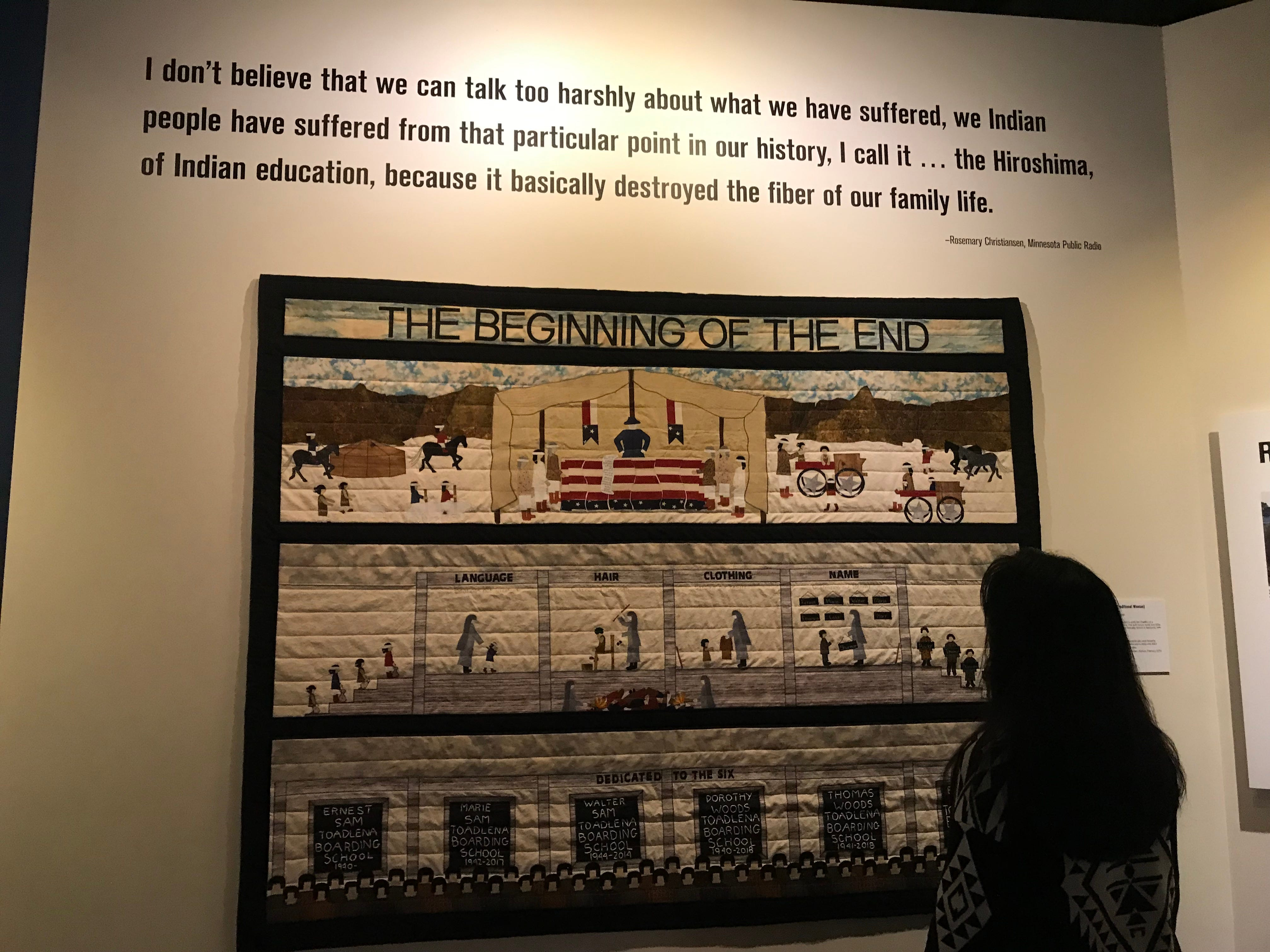 """Patty Talahongva looks at quilt made by Navajo weaver Susan Hudsan in honor of her family who went to boarding schools. The quilt is part of the Heard Museum's """"Away From Home: American Indian Boarding School Stories"""" exhibit."""