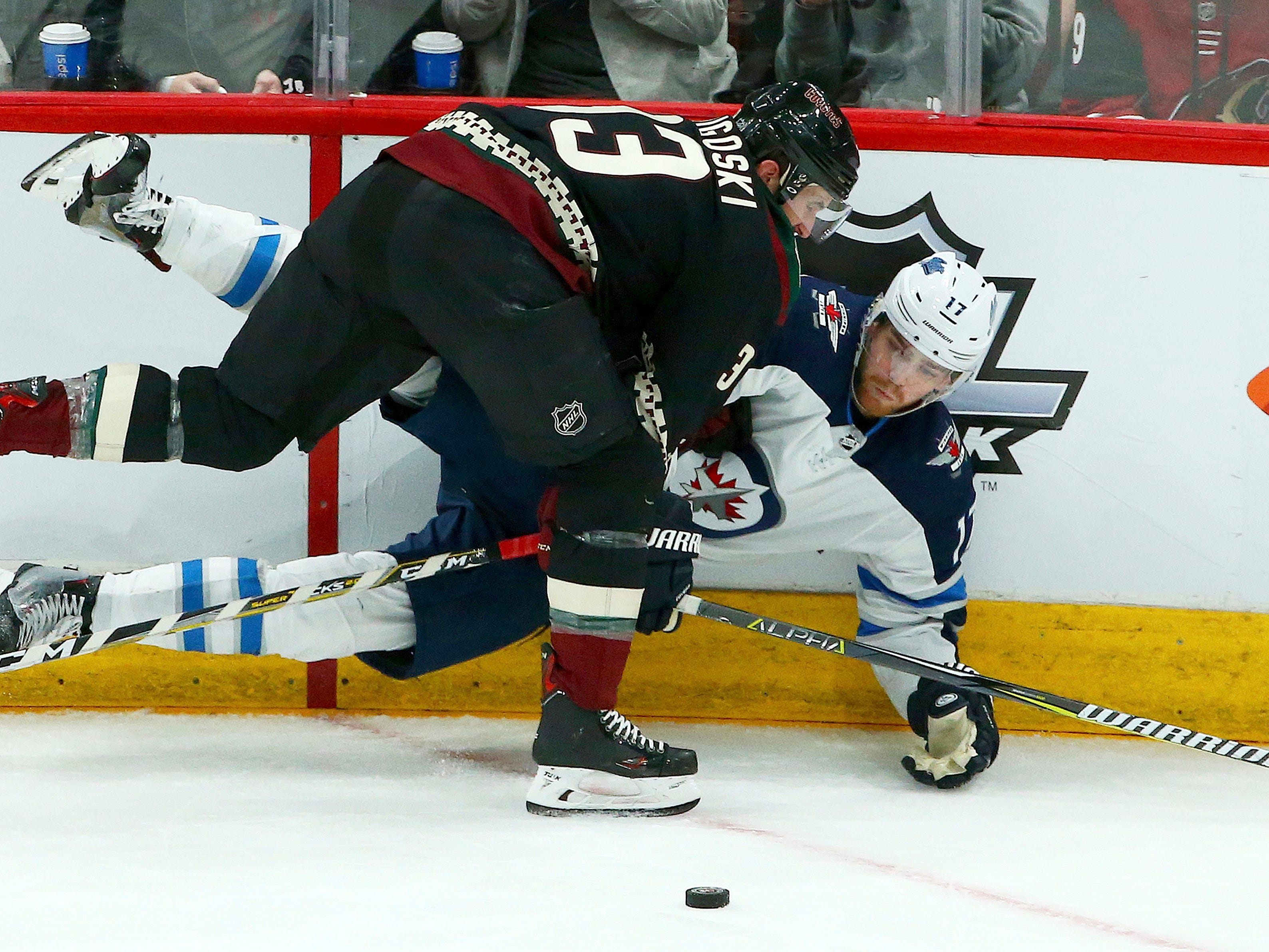 Arizona Coyotes defenseman Alex Goligoski, front, sends Winnipeg Jets center Adam Lowry (17) to the ice during the second period of an NHL hockey game Sunday, Feb. 24, 2019, in Glendale, Ariz.